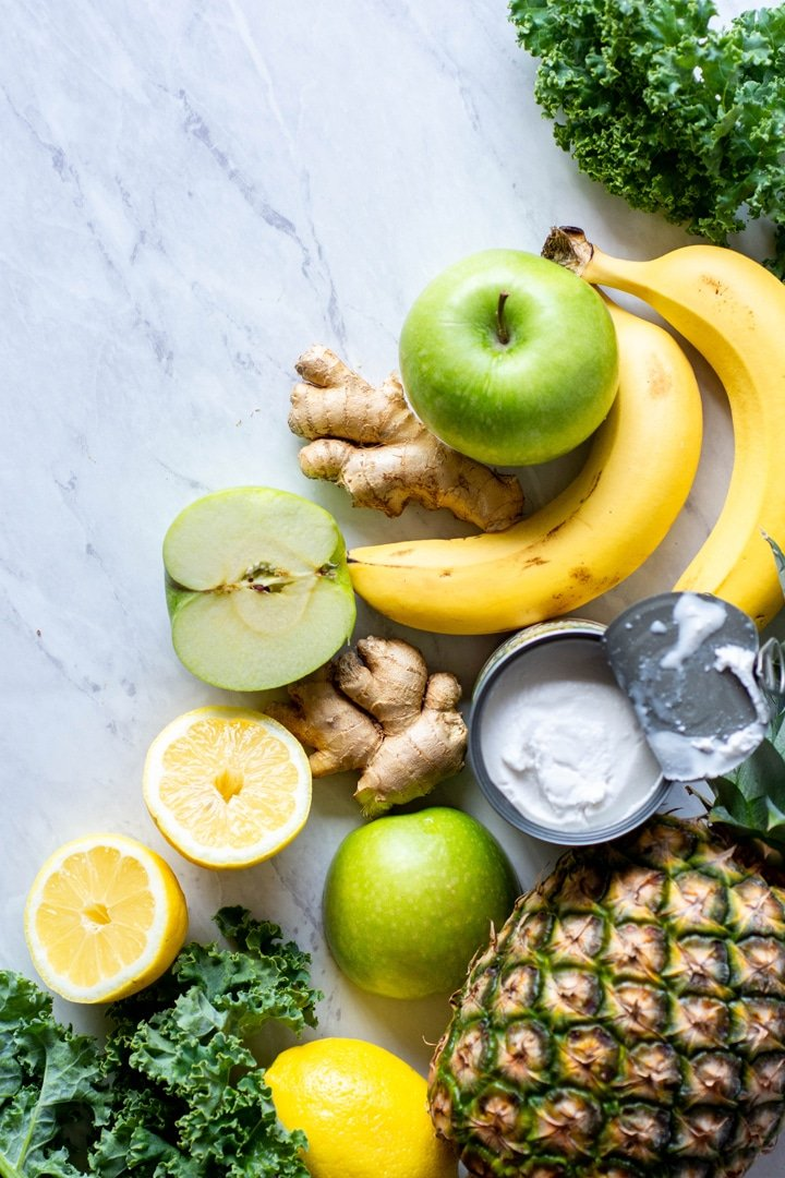 Array of tropical green smoothie ingredients spread out on a marble background. Cut apple, ginger, cut lemon, bananas, pineapple, and an open can of coconut milk.