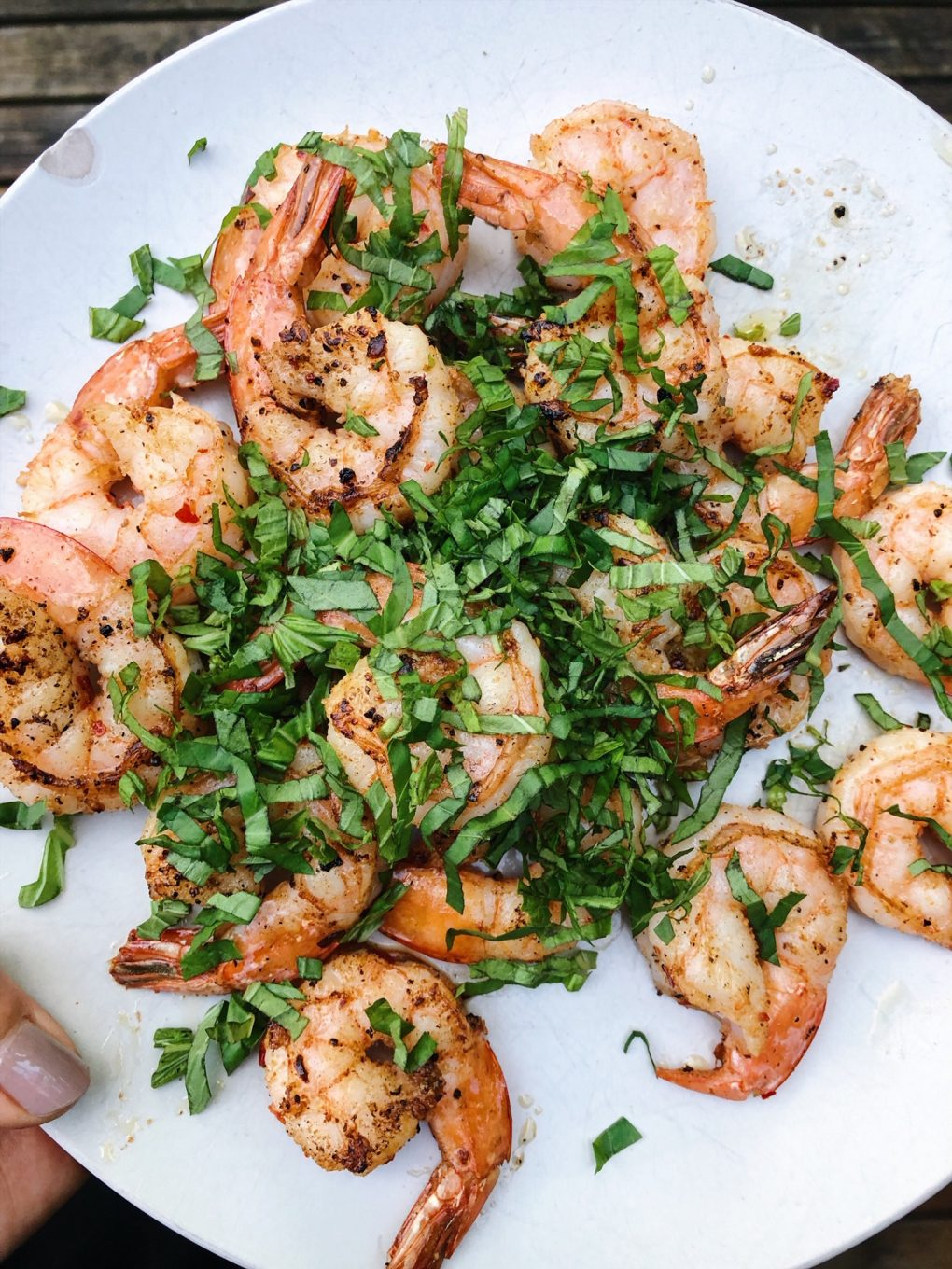 A white plate filled with seasoned shrimp and topped with chopped fresh basil