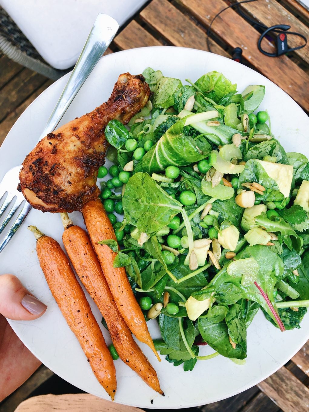 Holding a white plate outside with a chicken drumstick, roasted carrots, and a big green salad.