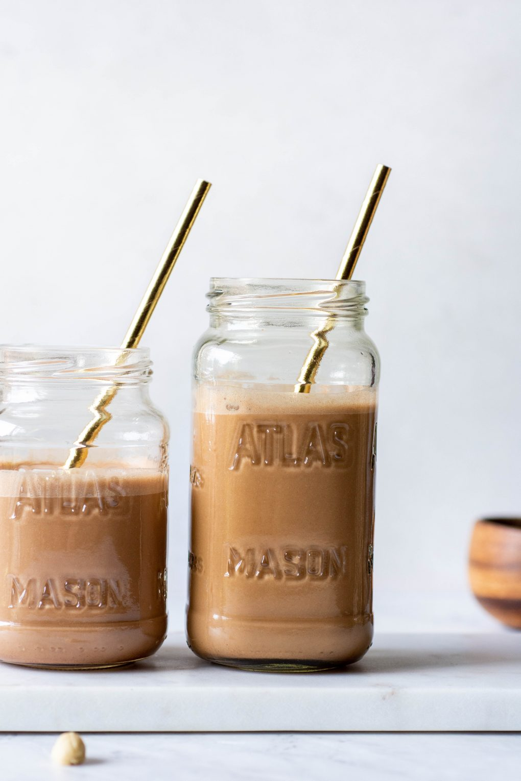 A close up shot of two side by side mason jars with chocolate cashew milk on a white background