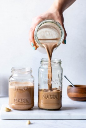 Pouring chocolate cashing milk into a tall mason jar next to an already filled mason jar on a white background
