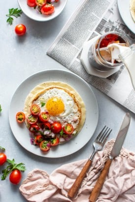 Two plates with open faced fried egg and hummus breakfast tacos topped with a simple tomato salad. Sitting on top of a newspaper on a light colored background next to a fork and knife, and someone pouring milk into an iced coffee.