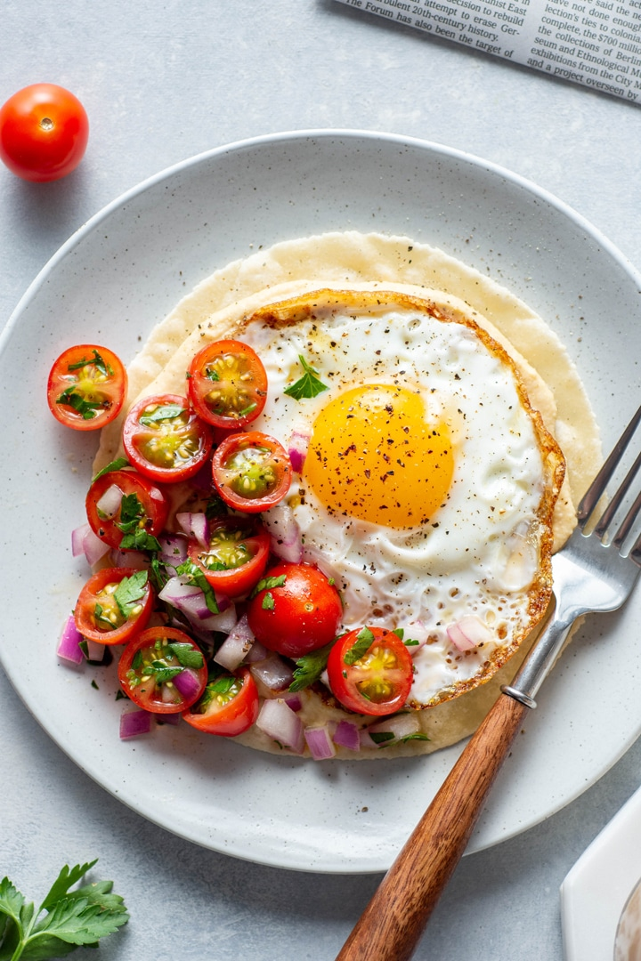 A close up view of a plate with open faced fried egg and hummus breakfast taco topped with a simple tomato salad. Sitting on top of a newspaper on a light colored background