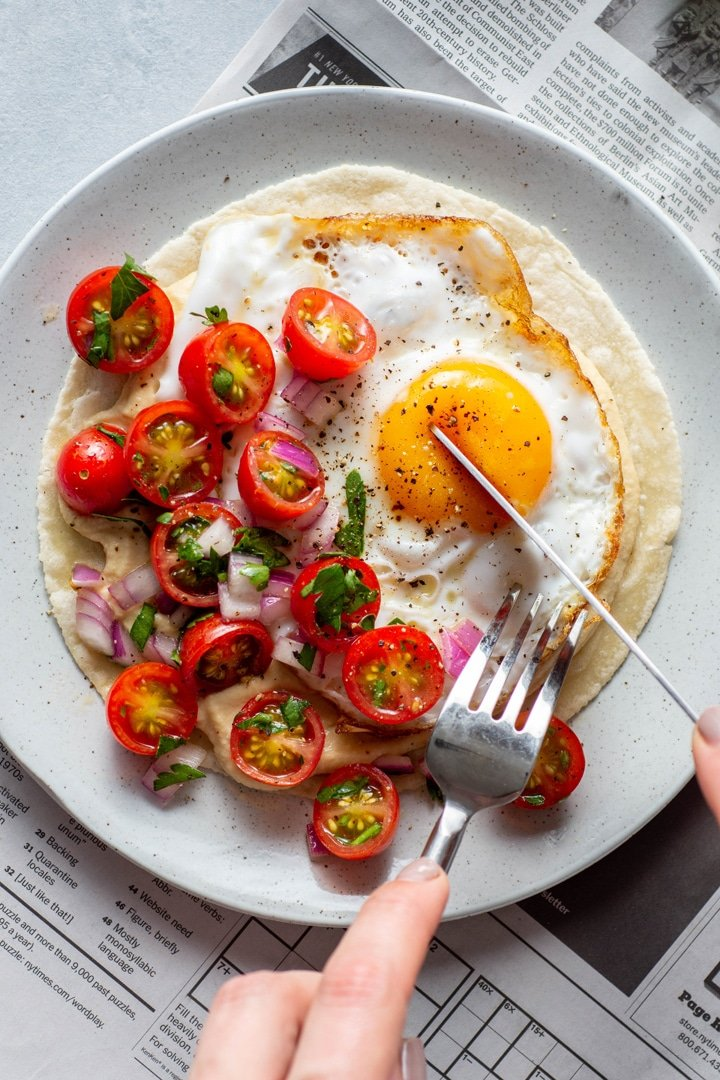 A close up view of a plate with open faced fried egg and hummus breakfast taco topped with a simple tomato salad. Sitting on top of a newspaper on a light colored background with someone cutting into the fried egg with a knife and fork