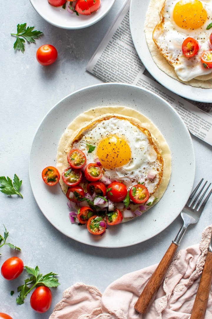 Two plates with open faced fried egg and hummus breakfast tacos topped with a simple tomato salad. Sitting on top of a newspaper on a light colored background next to a fork and knife.