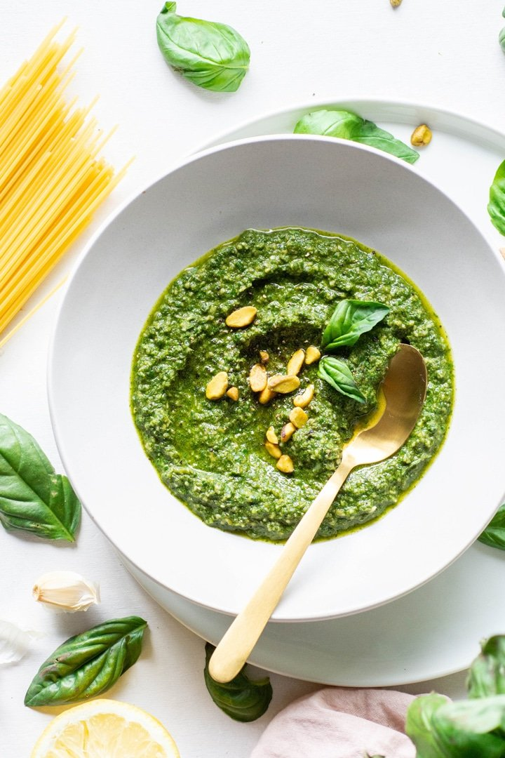 Overhead view of a white bowl of pistachio basil pesto topped with fresh basil and pistachios on a white background next to scattered basil leaves and a bundle of uncooked spaghetti