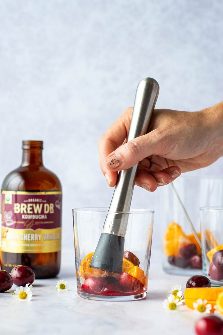 Muddling fresh dark cherries and tangerines in a glass against a light blue background next to a bottle of dark cherry vanilla Brew Dr. kombucha