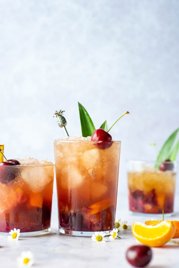 Side view of two side by side tropical kombucha cocktails with pineapple leaves and cherries on a light blue background