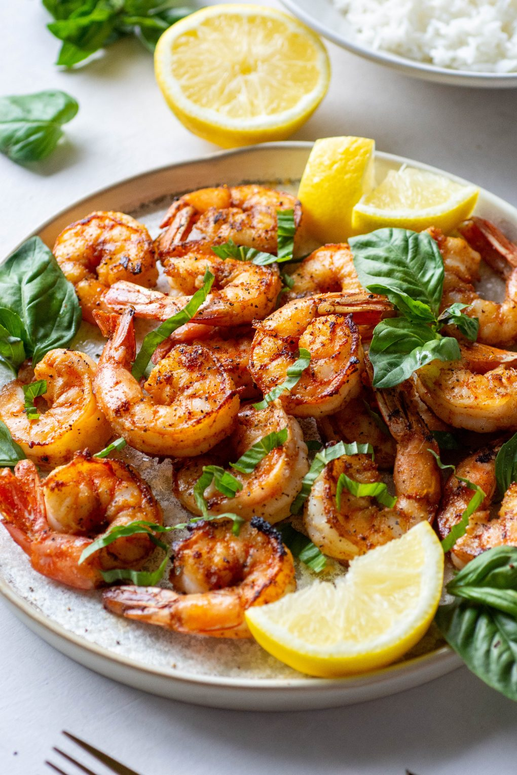 Close up side angle of a plate of seared shrimp topped with fresh basil and lemon wedges next to a bowl of white rice on a light background