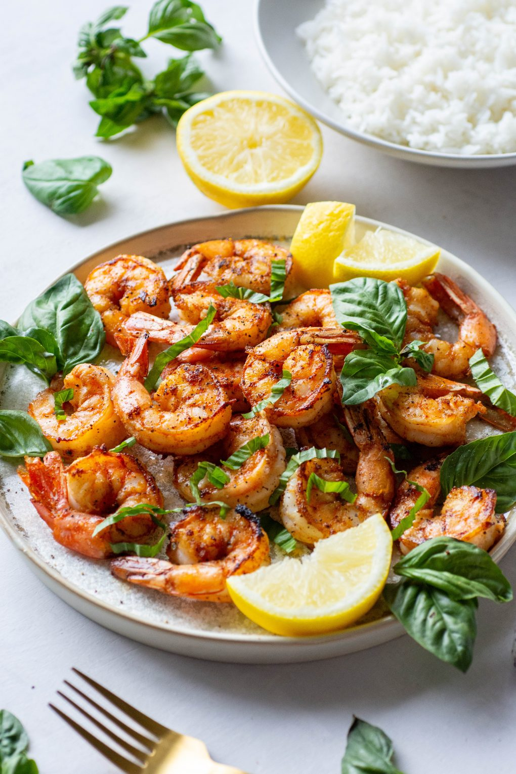 Side angle of a plate of seared shrimp topped with fresh basil and lemon wedges next to a bowl of white rice on a light background