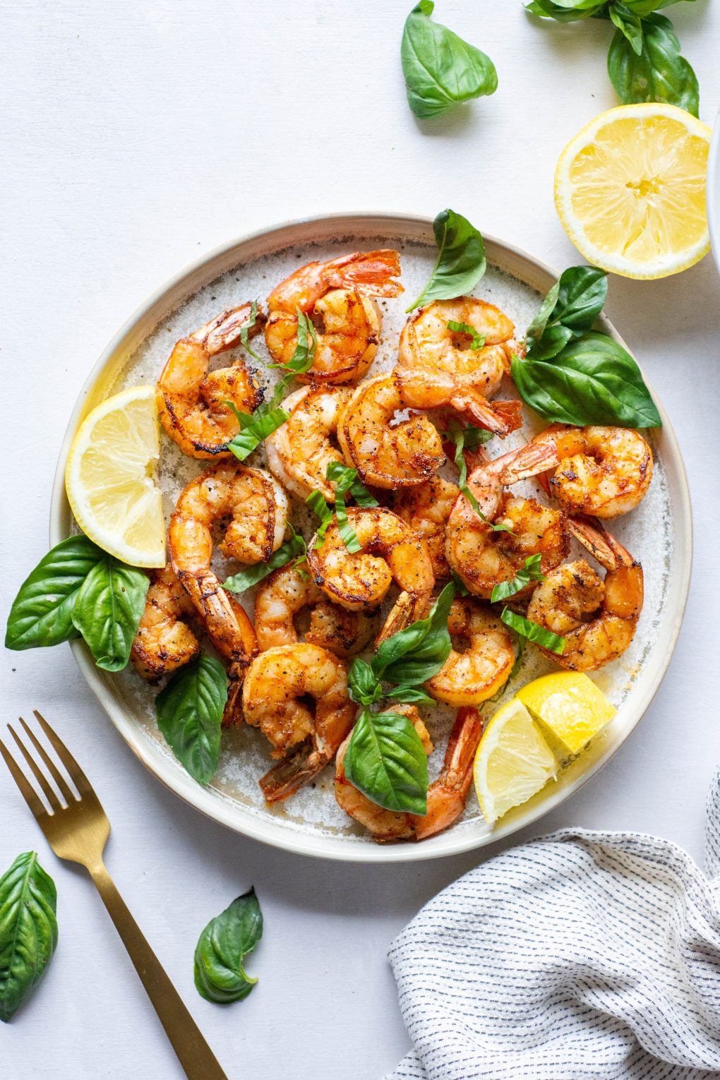 Plate of seared shrimp topped with fresh basil and lemon wedges on a light background next to loose basil leaves, a fork, and a striped dish towel