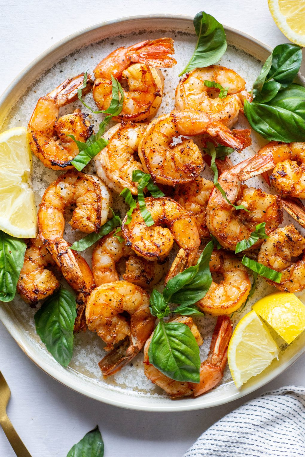 Plate of seared shrimp topped with fresh basil and lemon wedges on a light background