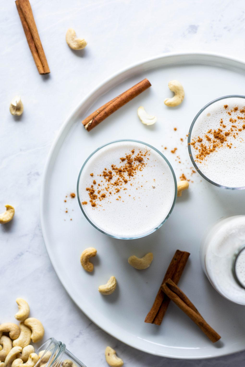 Overhead shot of two side by side glasses of cashew milk sprinkled with cinnamon on white plate on a marble background next to a cinnamon stick and some scattered cashews