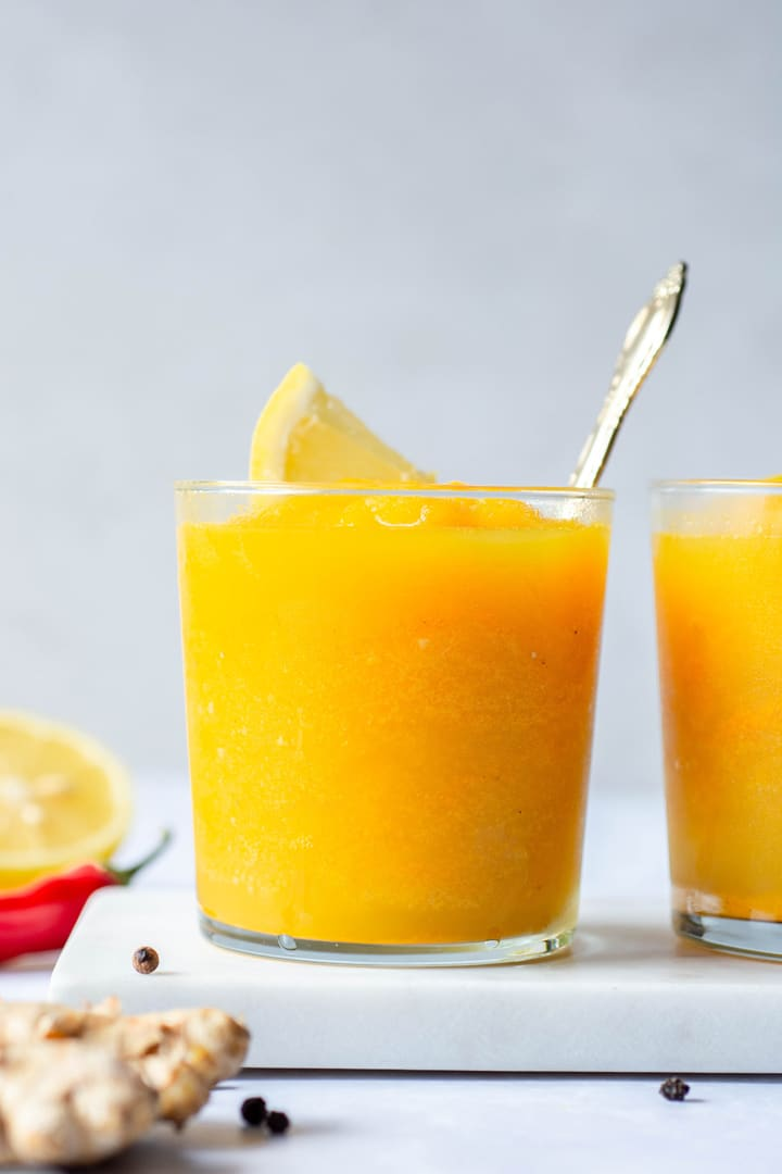 Close up shot of a bright yellow turmeric slushy with a lemon wedge and a spoon in a short clear glass against a white background