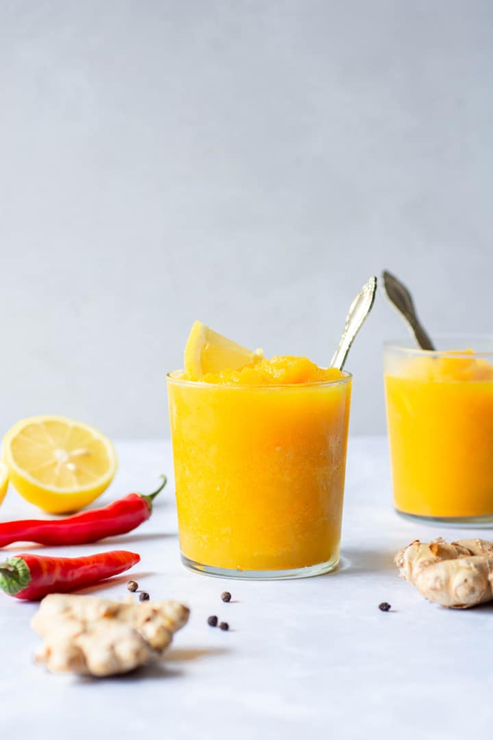 A small clear glass of a bright yellow turmeric slushy with a lemon wedge and spoon against a white background surrounded by lemon halves, red chilies, ginger, and black peppercorns