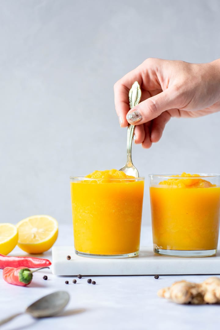 Hand dipping a spoon into a bright yellow turmeric slushy against a white background next to another slushy and lemon halves, ginger, chilies, and black peppercorns
