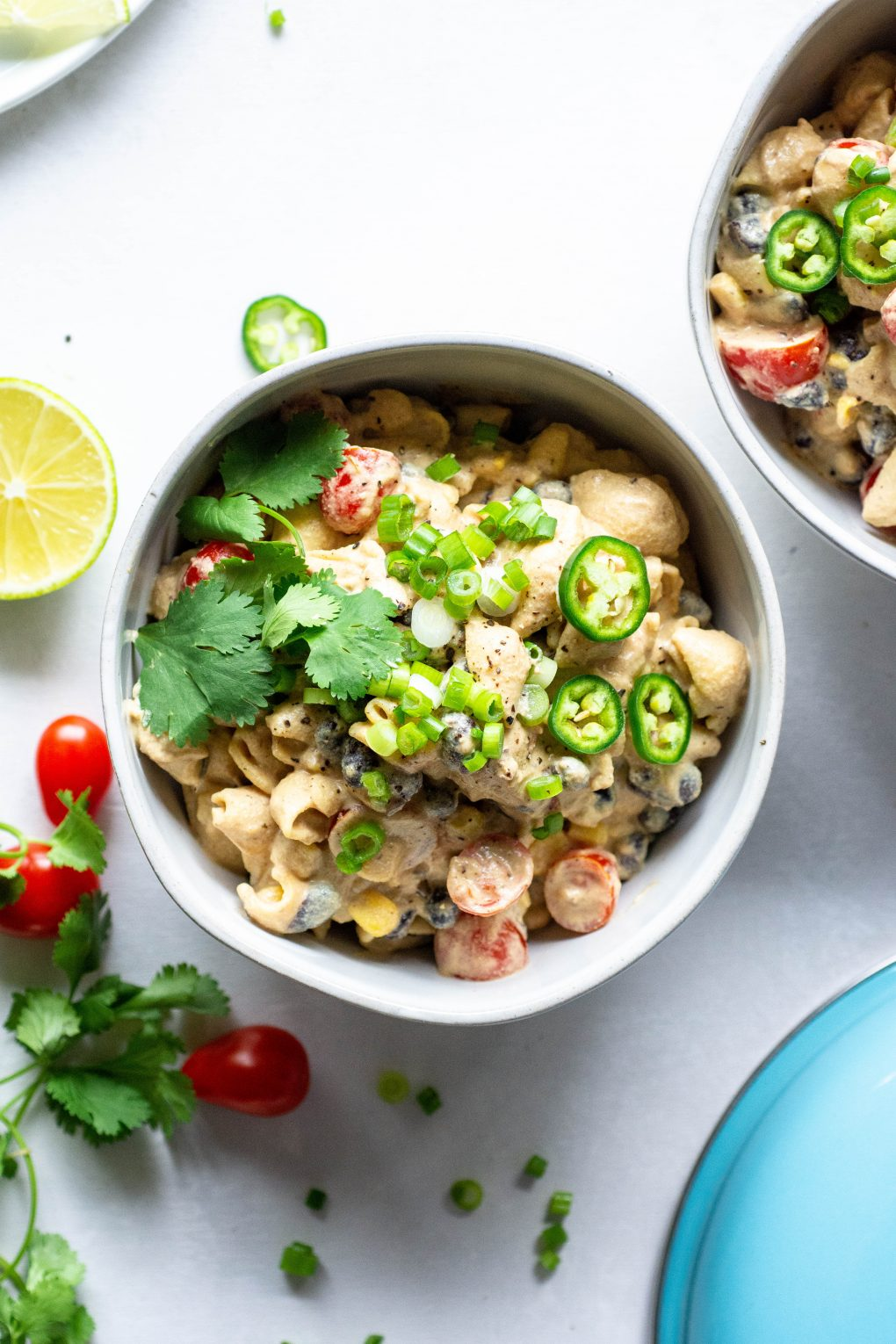 A close up shot of a bowl of vegan mexican mac and cheese topped with green onions, jalapeno, and fresh cilantro. On a light background surrounded by sliced lime, cherry tomatoes, and fresh herb.