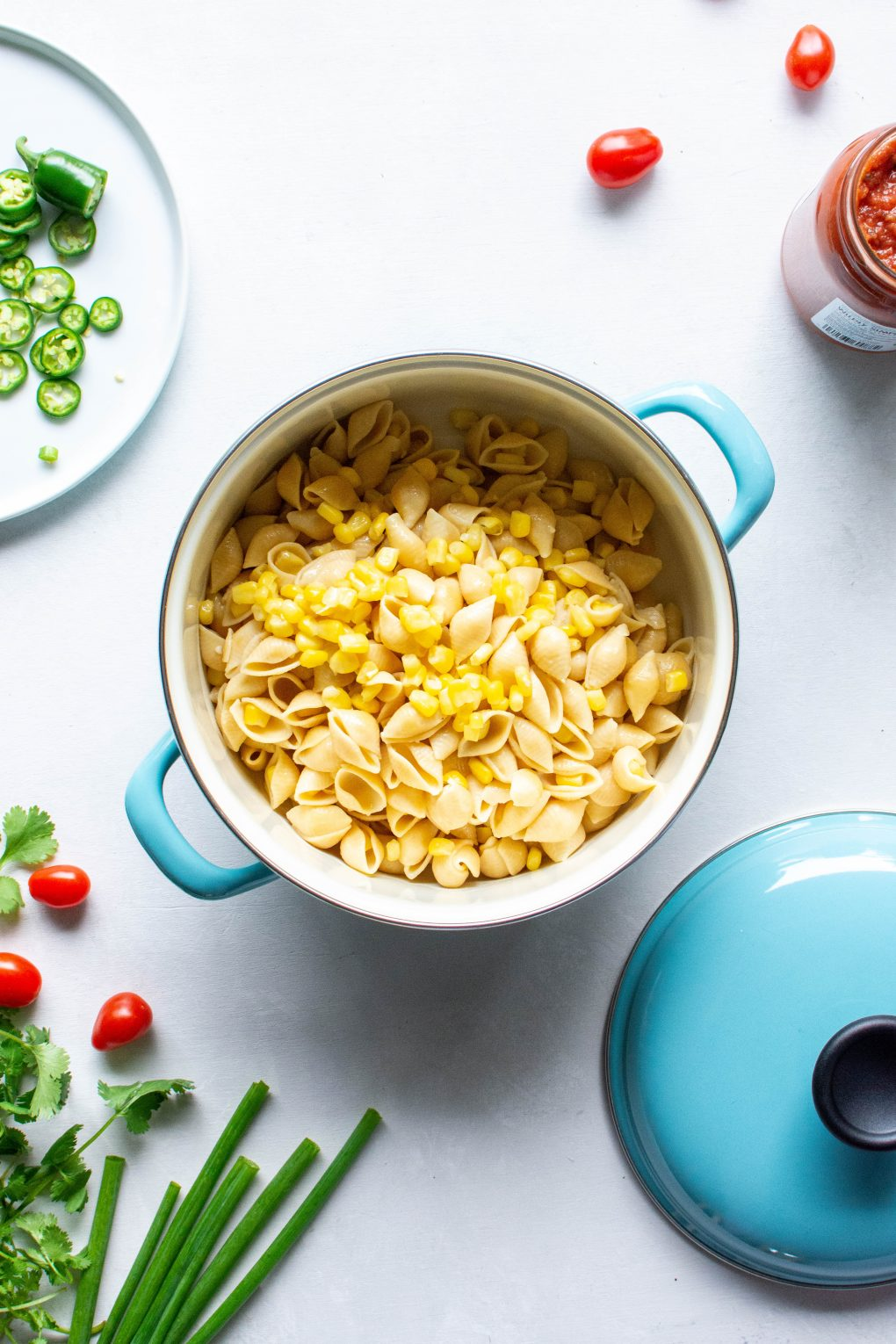A blue pot of pasta and corn surrounded by cherry tomatoes, green onions, and fresh herbs on a white background.