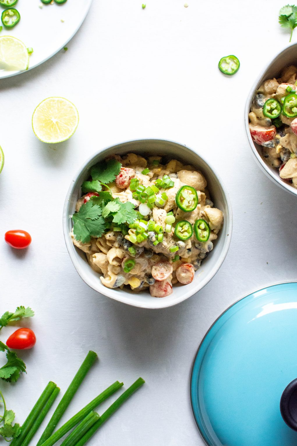Two side by side bowls of vegan mexican mac and cheese topped with green onions, jalapeno, and fresh cilantro. On a light background surrounded by sliced lime, cherry tomatoes, and fresh herb.