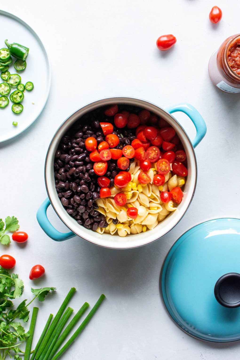 A blue pot of pasta, corn, black beans, and halved cherry tomatoes surrounded by cherry tomatoes, green onions, and fresh herbs on a white background.