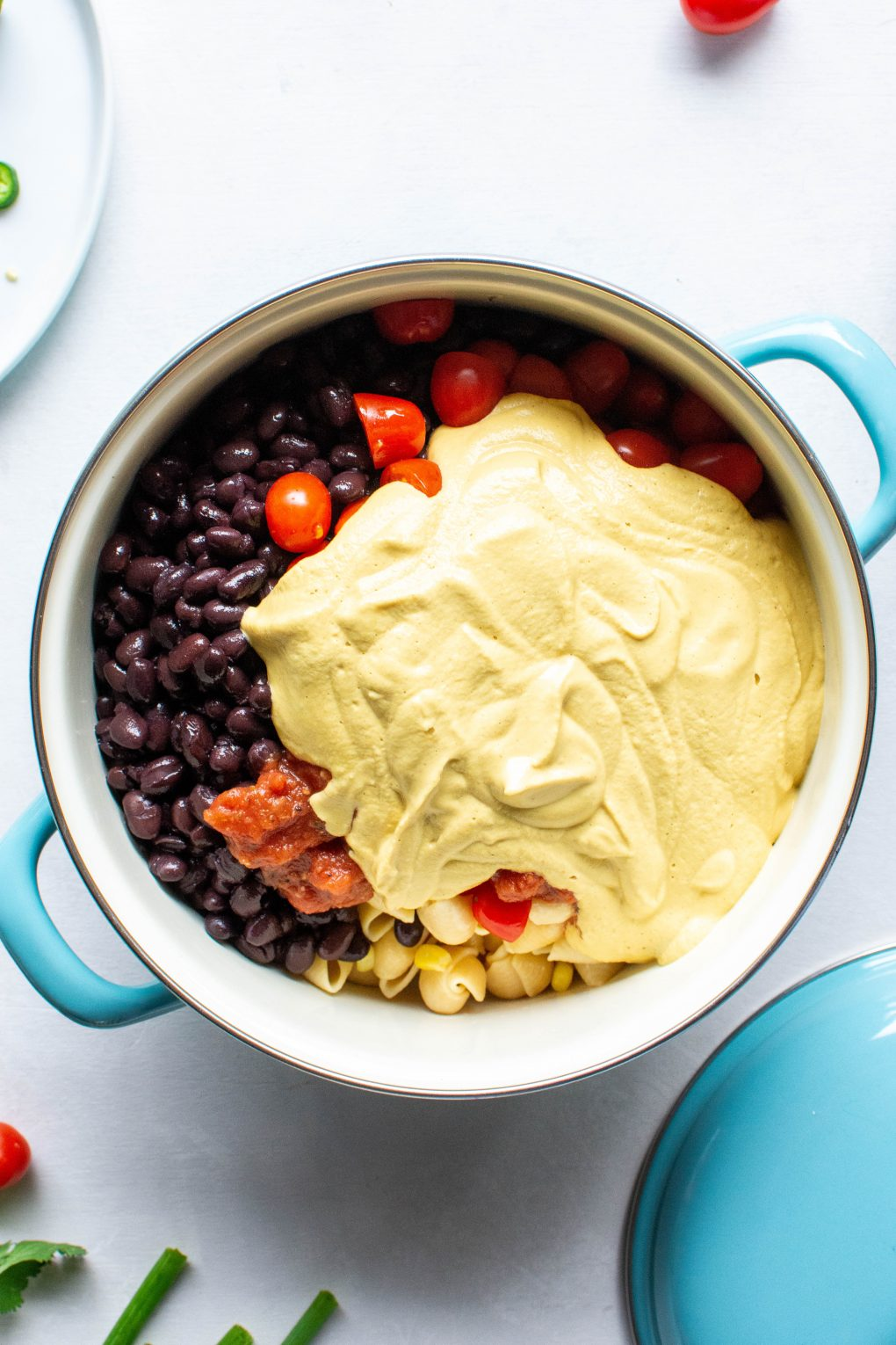 A blue pot of pasta, corn, black beans, halved cherry tomatoes, and cashew cheese sauce, surrounded by cherry tomatoes, green onions, and fresh herbs on a white background.