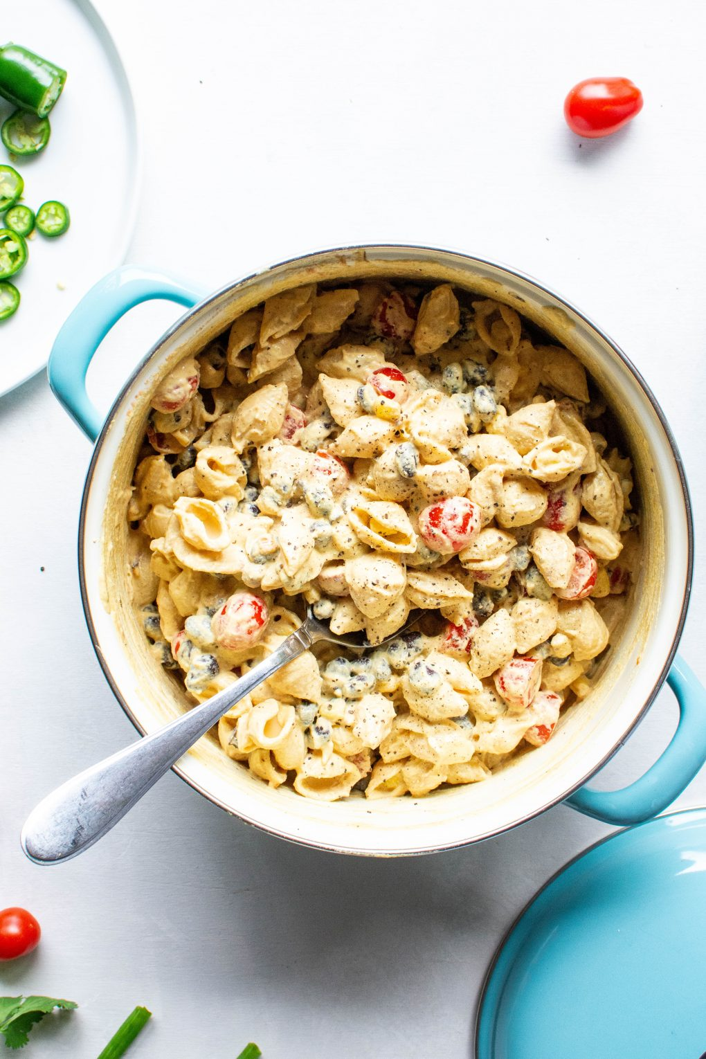 A blue pot of pasta, corn, black beans, halved cherry tomatoes, and cashew cheese sauce all mixed together surrounded by cherry tomatoes, green onions, and fresh herbs on a white background.