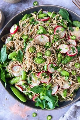 Close up shot of vegan soba noodle salad with vegetables and herbs - sugar snap peas, radishes, chilies, and sesame seeds on a moody grey background