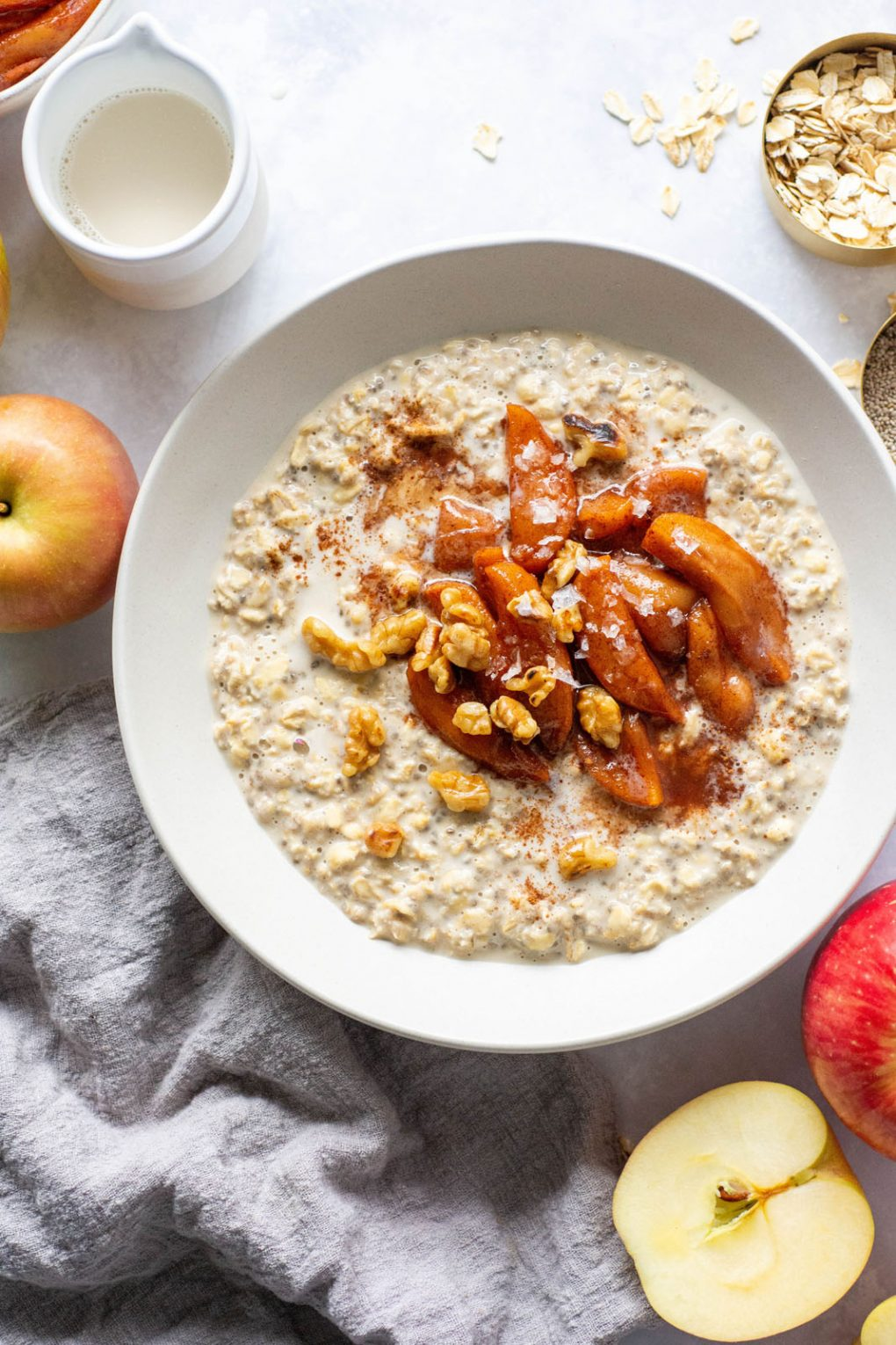 Large white bowl of salted caramel apple overnight oats topped with a big scoop of baked cinnamon apples, walnuts, and flaky sea salt. Bowl is on a light background surounded by cut apples, and bits of walnuts.