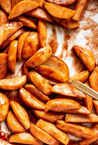 Close up of a white ceramic baking dish filled with paleo baked cinnamon apples with a gold spoon scooping them.
