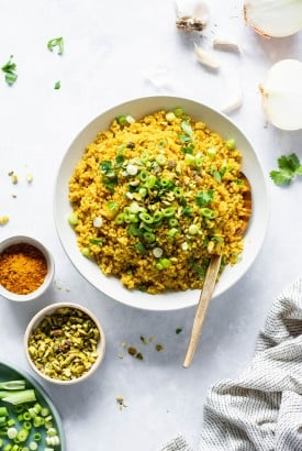 Big white bowl of bright yellow curried quinoa topped with cilantro, green onions, and pistachios. On a light colored background next to a small bowl of pistachios, a small bowl of curry powder, and an onion sliced in half. There's a large gold metal spoon in the bowl.