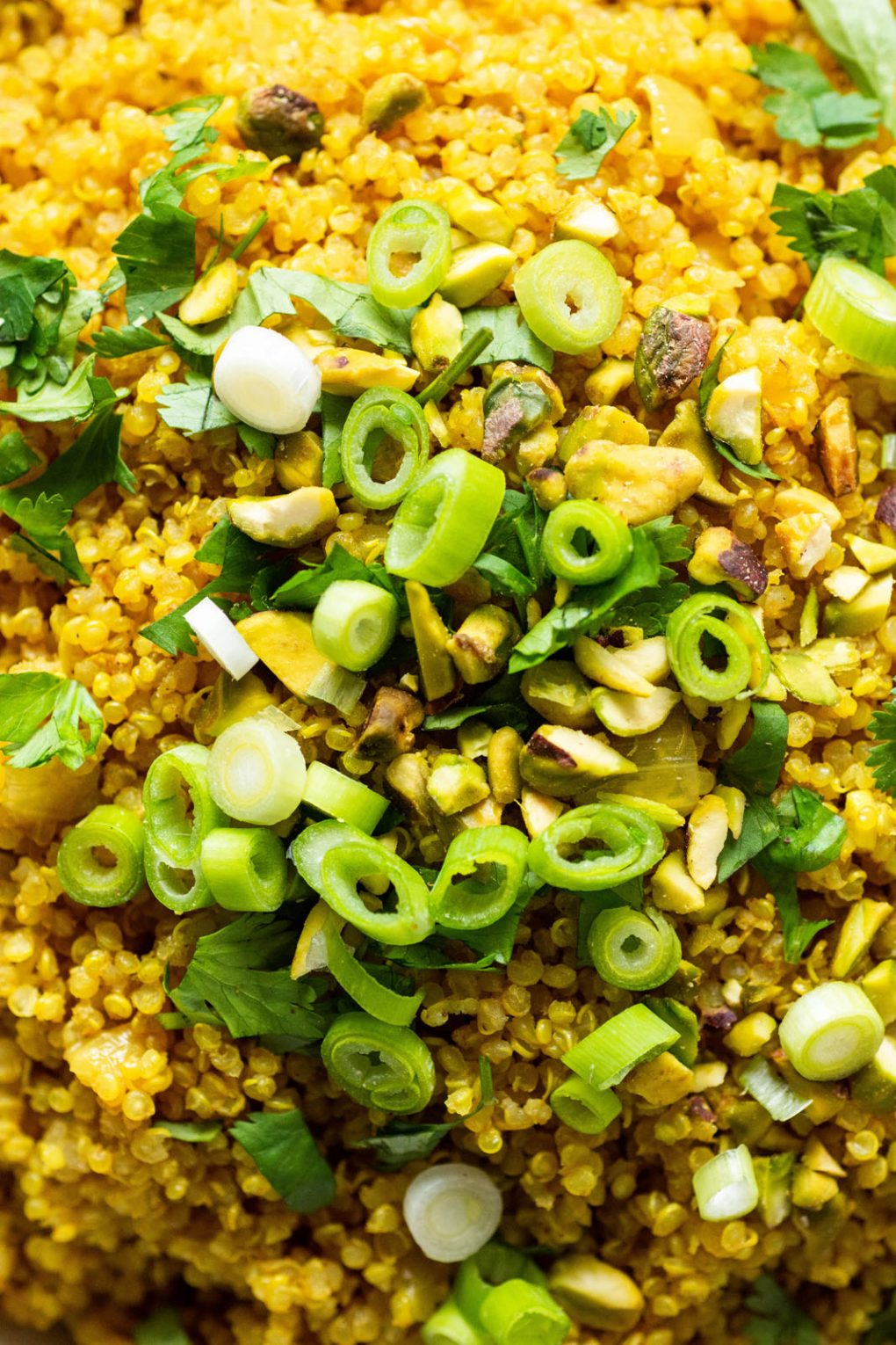 Close up shot of bright yellow curried quinoa topped with cilantro, green onions, and pistachios.