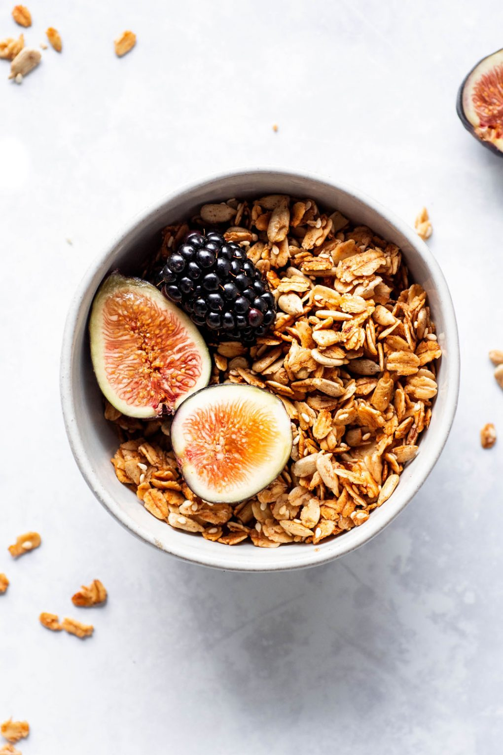 A small white bowl filled with maple sesame granola, cut figs, and blackberries. On a white background with scattered granola around the bowl.
