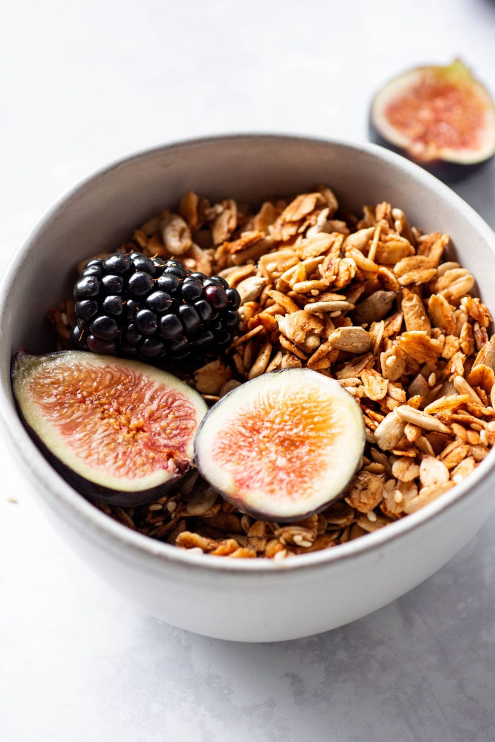 45 degree angle shot of a small white bowl filled with maple sesame granola, cut figs, and blackberries. On a white background with scattered granola around the bowl.