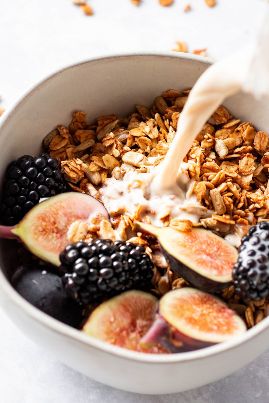 45 degree angle shot of a small white bowl filled with maple sesame granola, cut figs, and blackberries with milk pouring in. On a white background with scattered granola around the bowl.