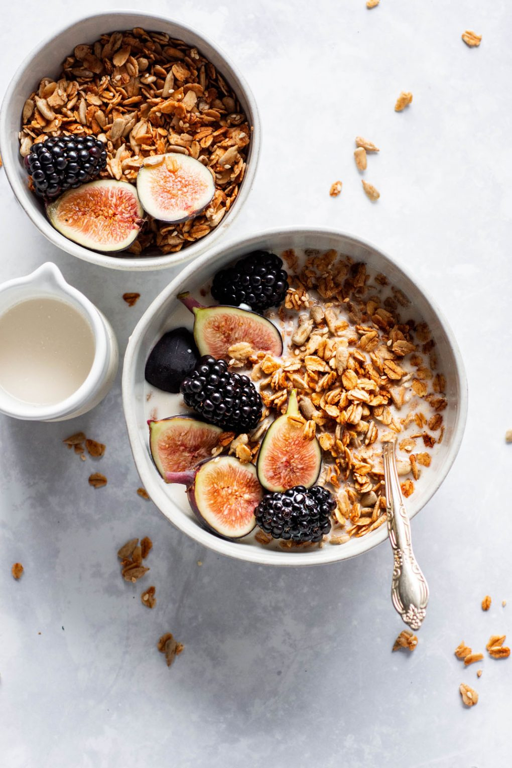 Overhead shot of two small white bowls filled with maple sesame granola, cut figs, and blackberries. Next to a small white pitcher of milk on a white background with scattered granola around the bowl.