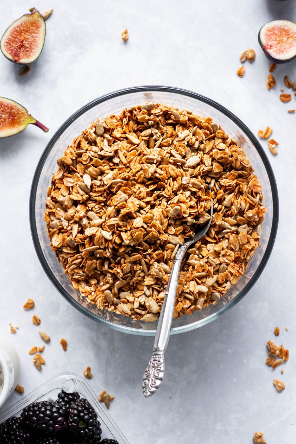 overhead shot of a large glass pyrex dish full of toasty granola with a silver spoon angled in. On a white background next to cut figs and scattered granola