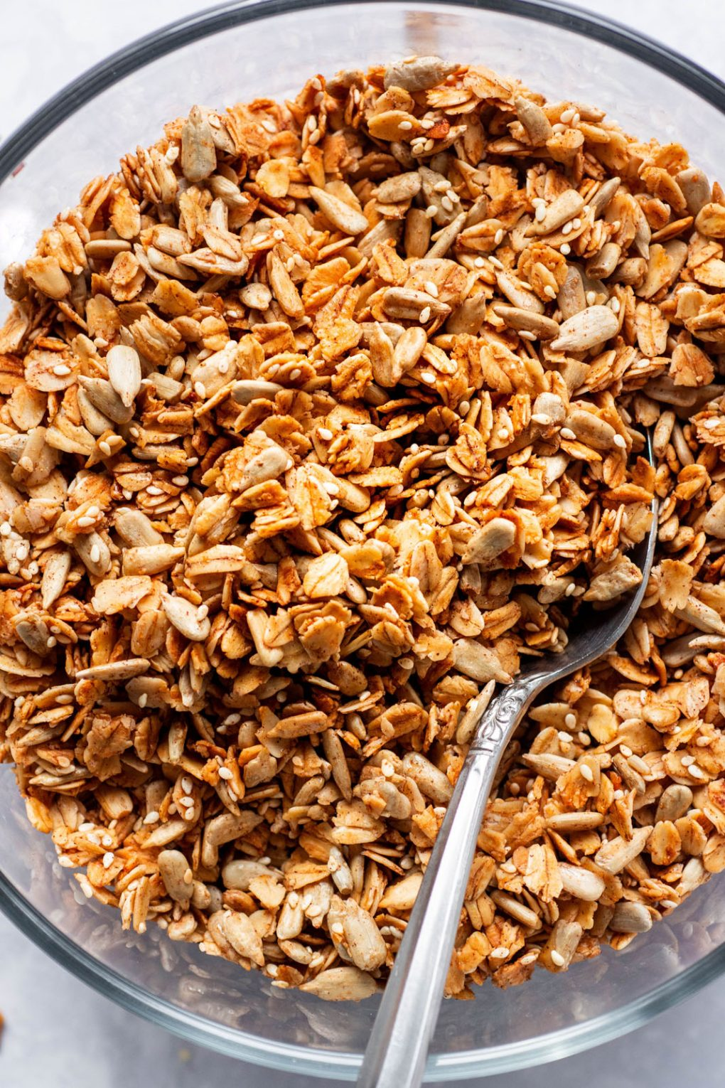 Close up overhead shot of a large glass pyrex dish full of toasty granola with a silver spoon angled in. On a white background.