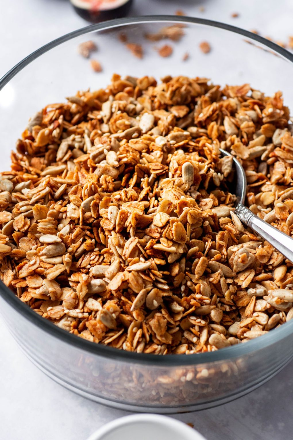 Side angle shot of a glass pyrex dish with toasty granola and a silver spoon digging in.