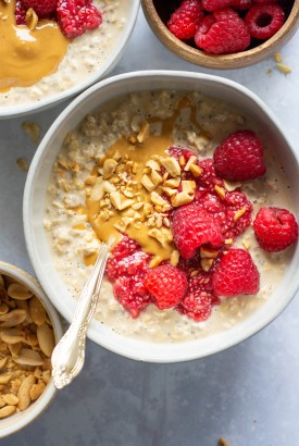 small white bowl of peanut butter overnight oats topped with a peanut butter drizzle, crushed peanuts, raspberry chia seed jam and fresh raspberries. In between a smaller bowl of raspberries, and a smaller bowl of peanuts.