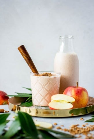 Glass full of cinnamon apple pie smoothie with a wooden handled spoon. Sitting in a gold rimmed round serving tray next to a larger jar of smoothie and surrounded by apples, scattered granola, greenery, and cinnamon sticks.