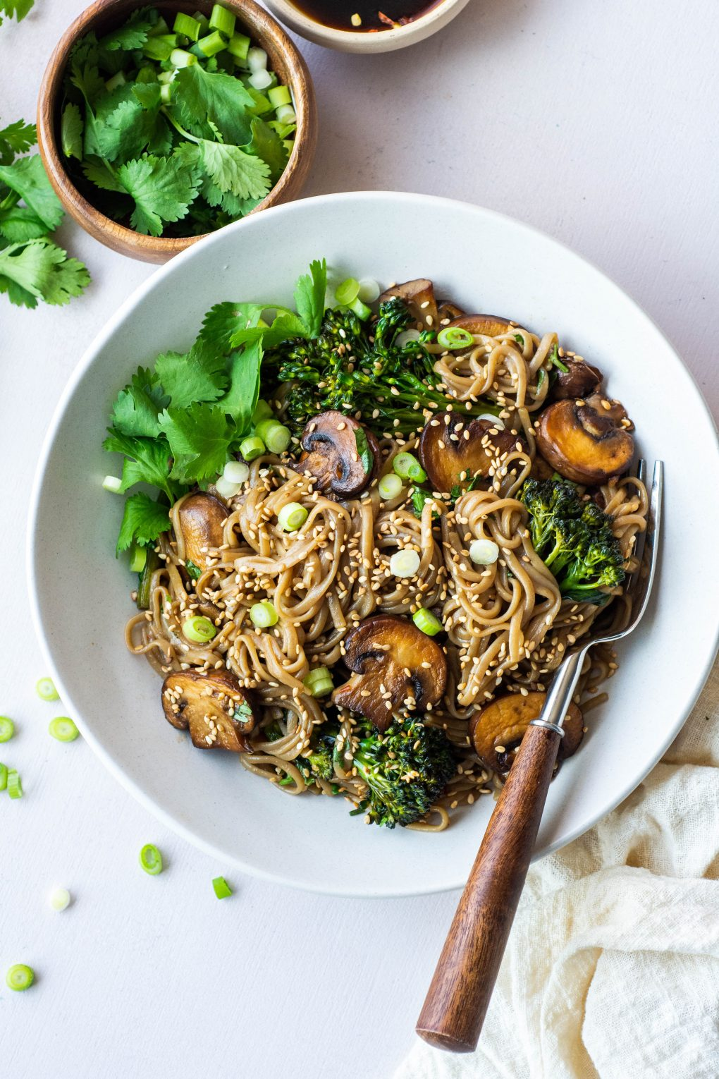 Overhead shot of a white bowl with a gluten free mushroom soba noodle stir fry topped with sesame seeds, green onions, and fresh cilantro. On a white background surrounded by a small bowl of cilantro, scattered green onions, and a white linen.