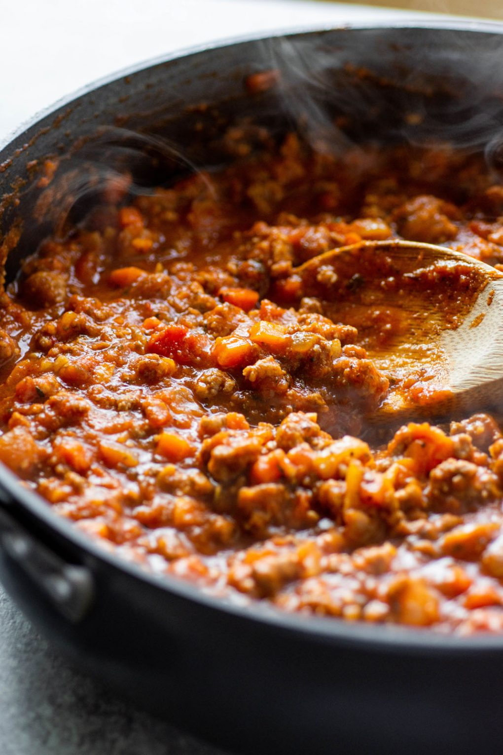 Side angle view of a skillet of pumpkin ragu pasta sauce with a wooden spoon dipping into the steaming sauce.