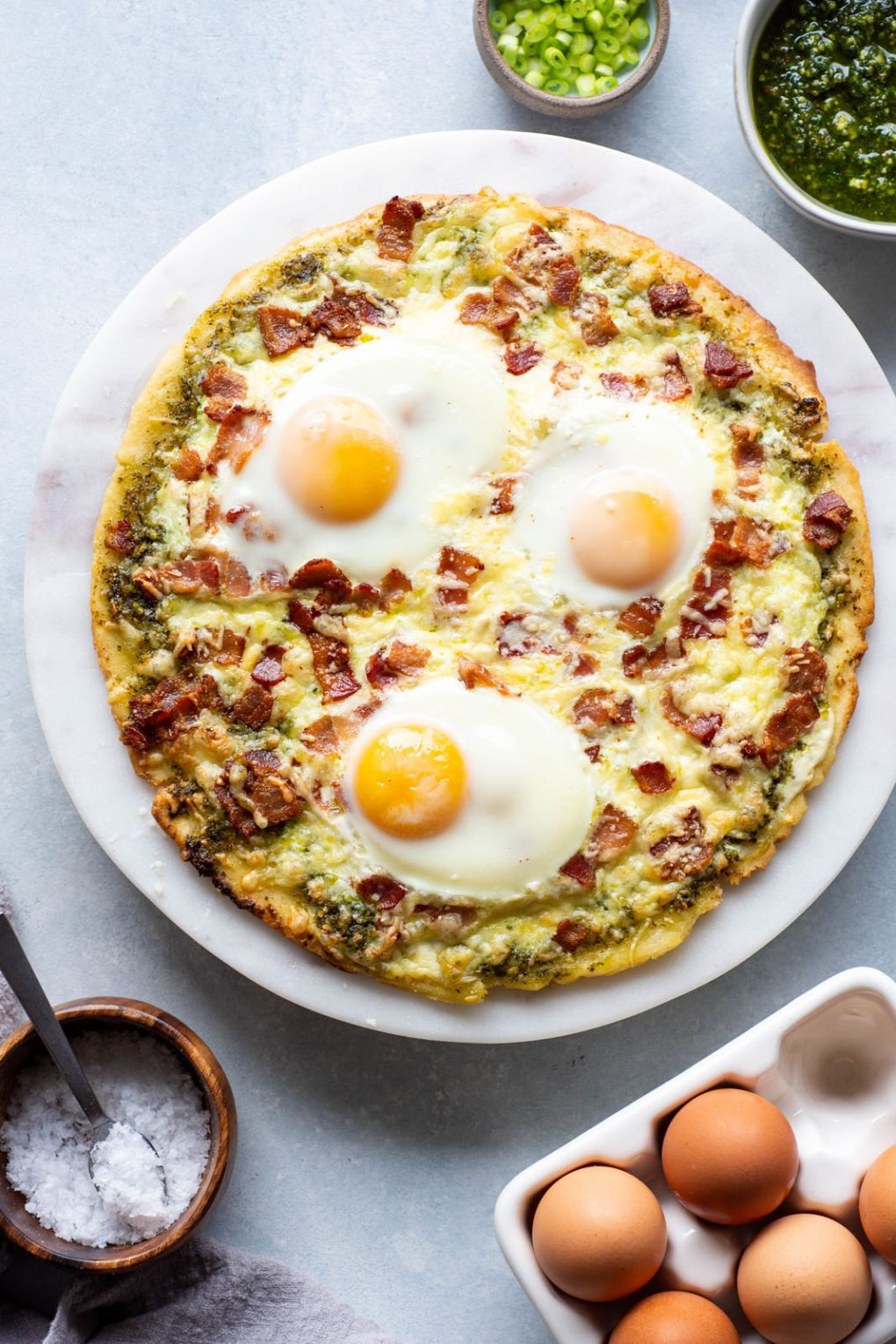 Overhead shot of cooked breakfast pizza. Topped with cheese, crispy bacon, sunny side up eggs. On a light colored marble serving tray and a light background. Next to a small bowl of sliced green onions, and another small bowl of pesto.