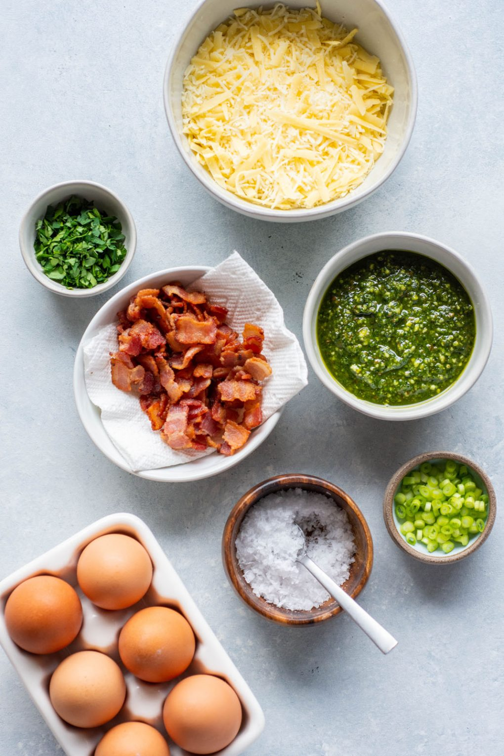 Assortment of bowls on a light colored background holding all the ingredients for the breakfast pizza. A bowl of cheese, a bowl of pesto, a bowl of herbs, a bowl of green onions, a bowl of cooked bacon, a bowl of sea salt, and a small dish of brown eggs.