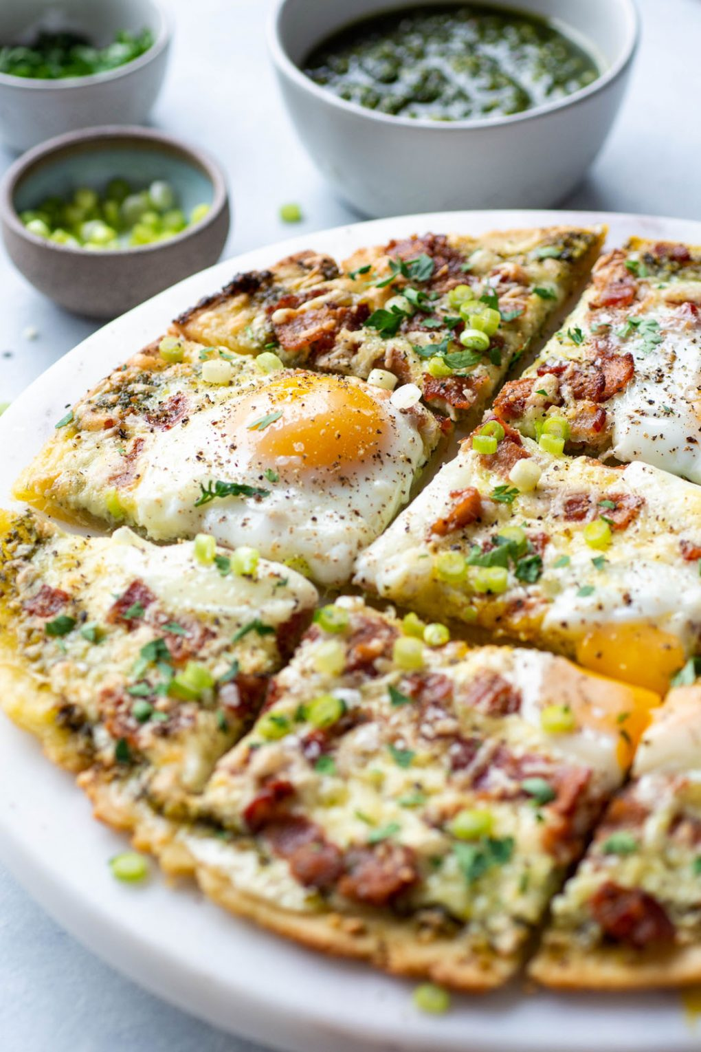 Side angle view of a breakfast pizza with melted cheese, crispy bacon, sunny side up eggs, and fresh herbs and green onions. On a light colored marble serving tray and a light background. Next to a small bowl of sliced green onions, and another small bowl of pesto.