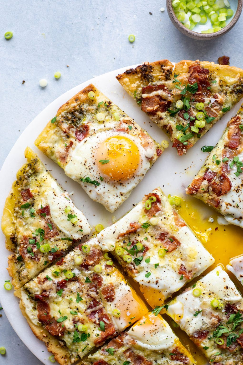 Overhead shot of a breakfast pizza. Topped with melty cheese, crispy bacon, sunny side up eggs, and fresh herbs and green onions. On a light colored marble serving tray and a light background.