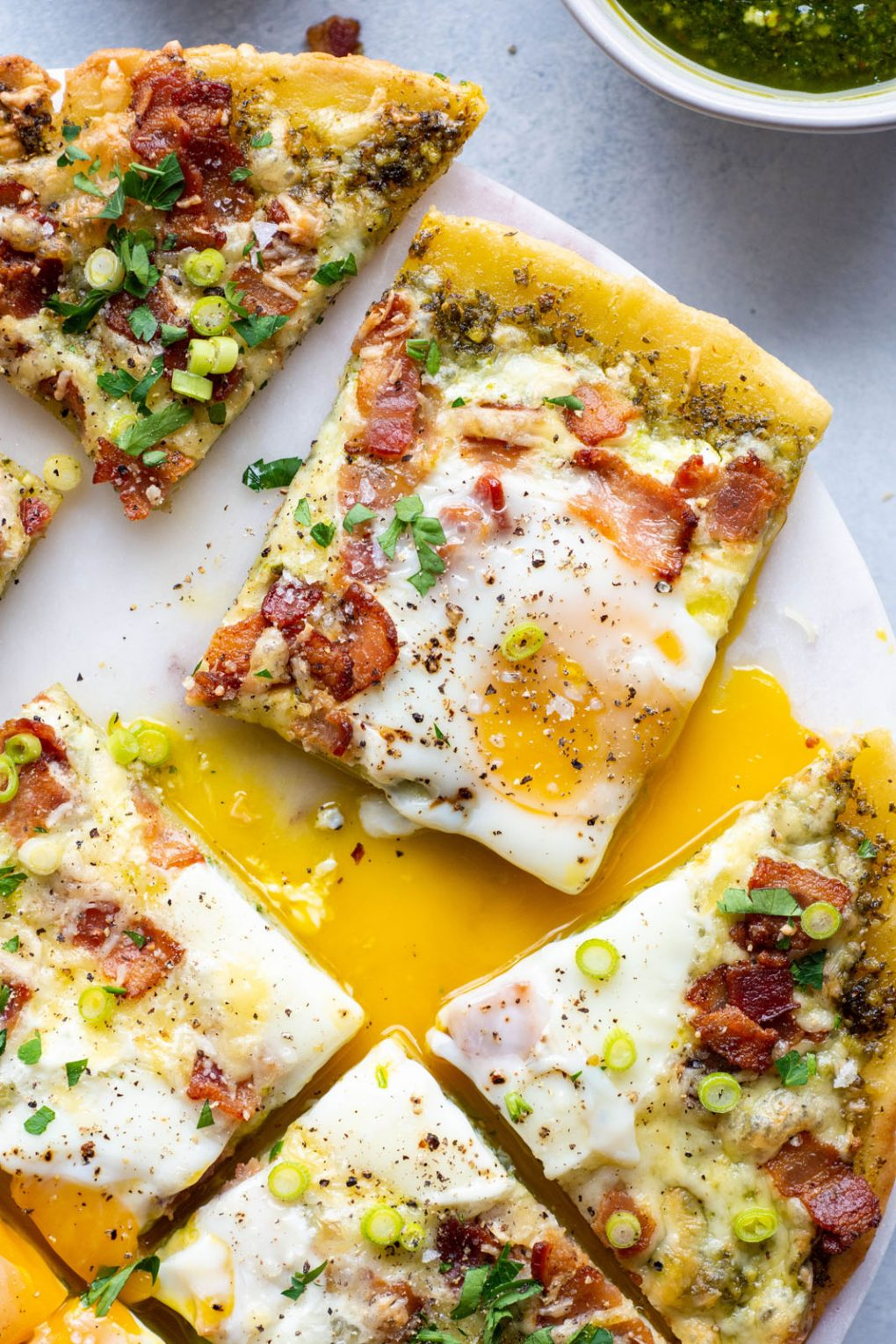 A close up overhead shot of a single square shaped piece of breakfast pizza pulled away from the rest of the pizza surrounded by runny egg yolk and topped with fresh herbs and green onion. On a light colored background.