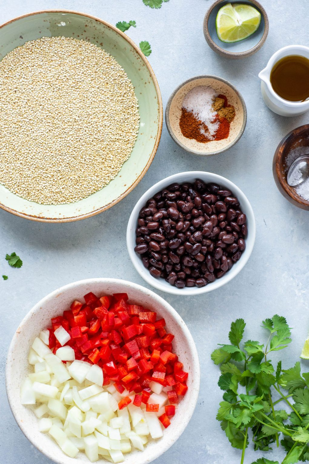 Overhead shot of various ingredients for southwest quinoa and black beans. Plate of white quinoa, a small bowl of spices, a bowl of black beans, a bowl of diced onion and red pepper, and fresh cilantro on a light colored background.