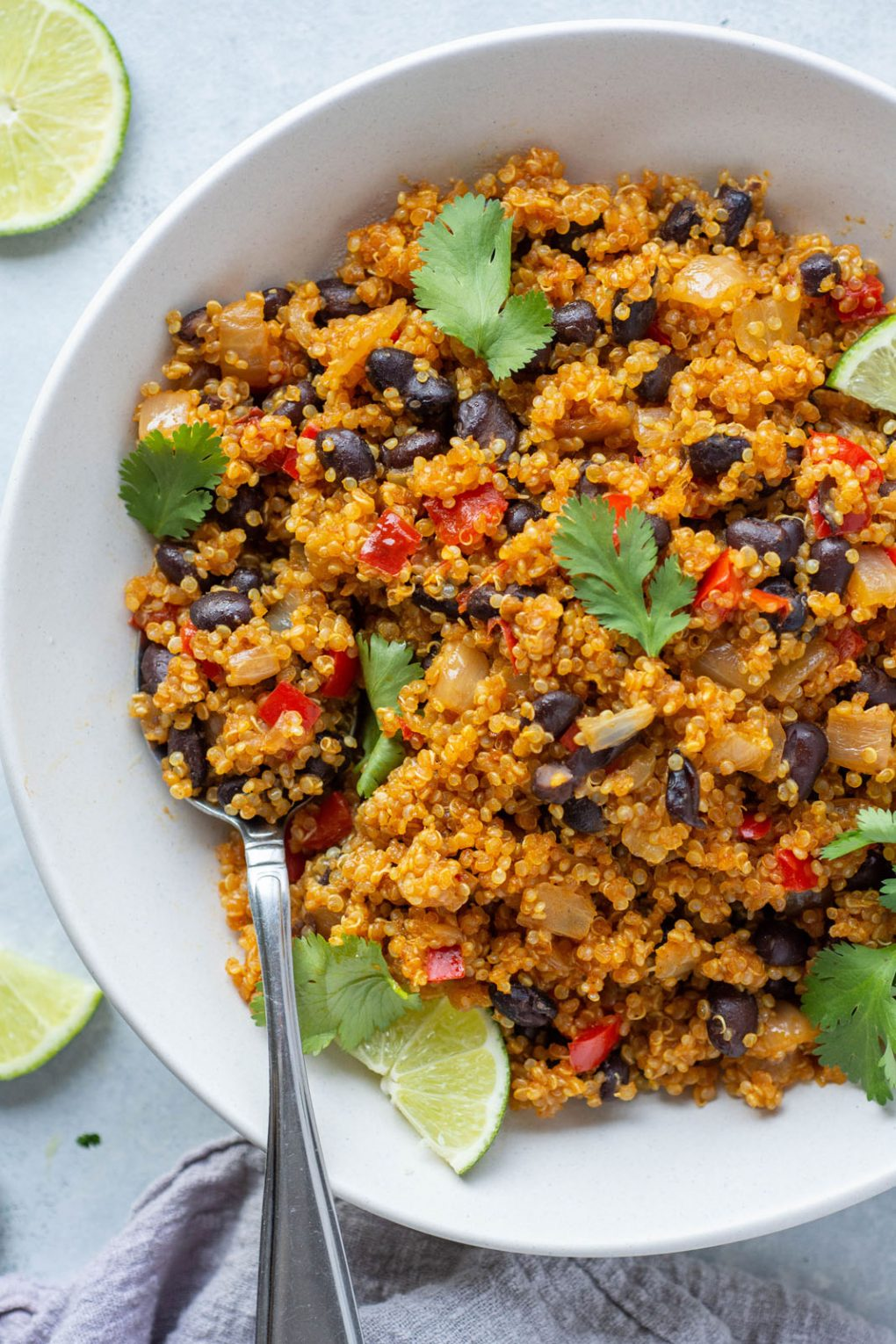 Overhead shot of southwest quinoa with black beans, diced red pepper, fresh cilantro, and garnished with lime wedges. In a white bowl on a light colored background.