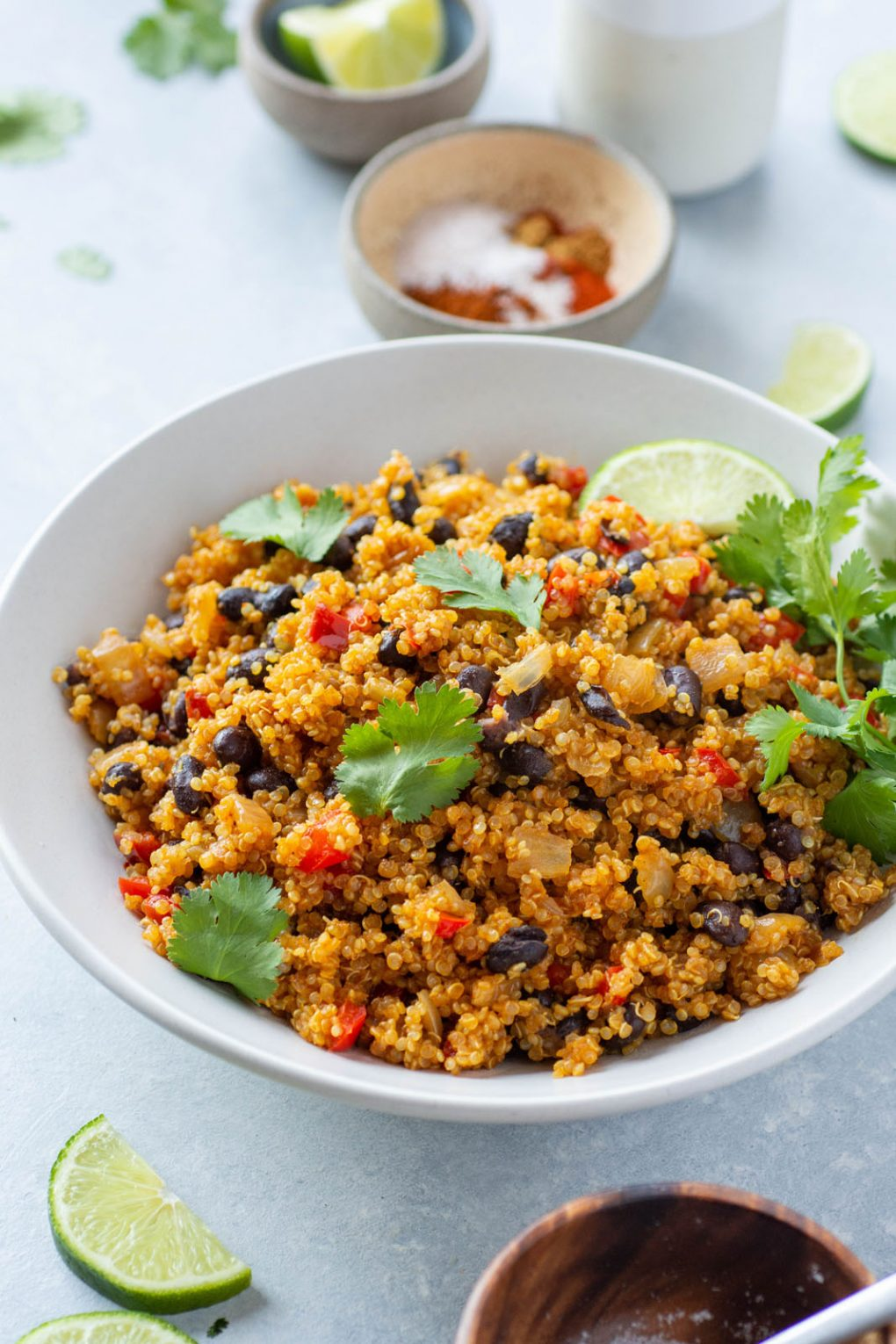 Side angle shot of southwest quinoa with black beans, diced red pepper, fresh cilantro, and garnished with lime wedges. In a white bowl on a light colored background.